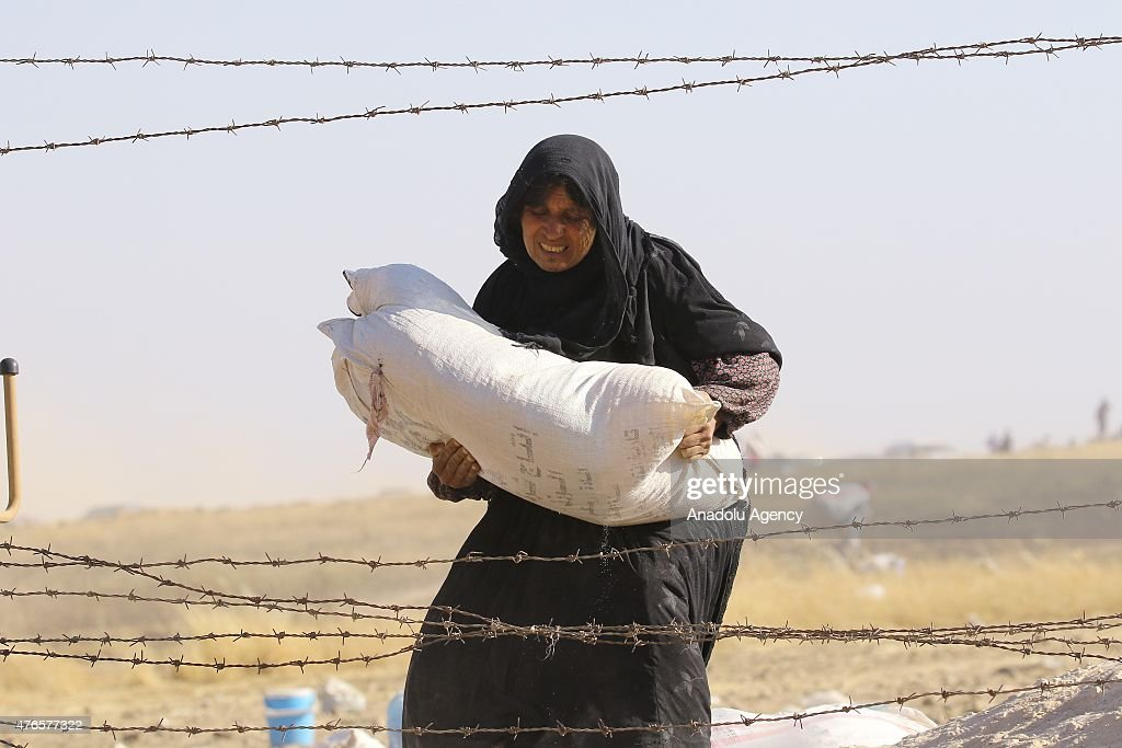 A Syrian woman carries her belongings as they cross into Turkey from the borderline in Akcakale district of Sanliurfa on June 10, 2015. Hundreds of Syrians who fled from Syria after clashes in Rasulayn region of Al-Hasakah, have crossed into Turkey since last week.