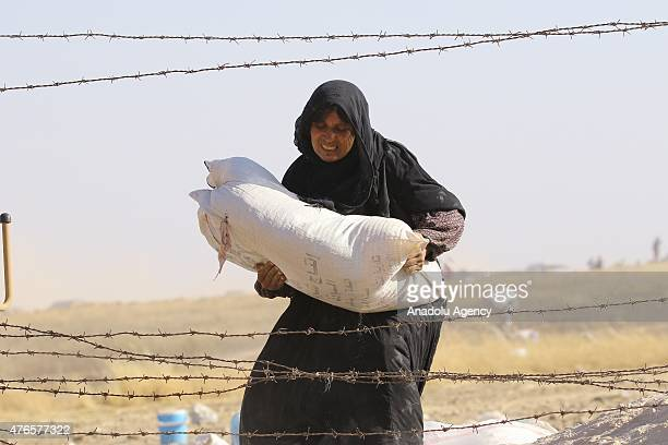 Syrian woman carries her belongings as they cross into Turkey from the borderline in Akcakale district of Sanliurfa on June 10 2015 Hundreds of...