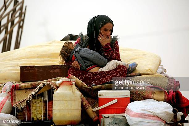 Syrian woman carries her child at a temporary refugee camp in the village of Ain Issa, housing people who fled Islamic State group's Syrian...