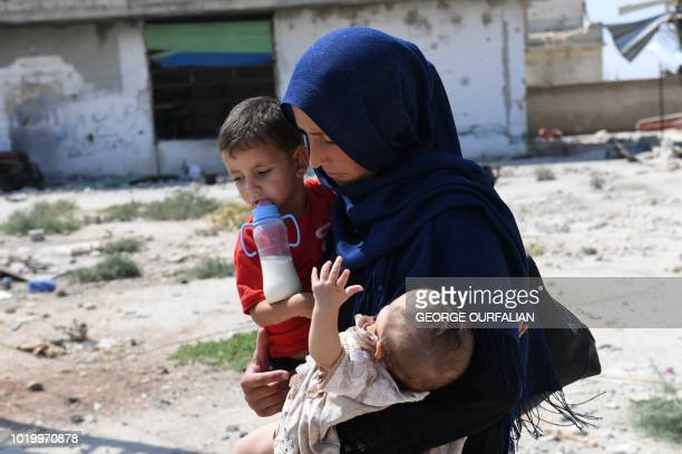 A Syrian woman carries her children as she walks at the Abu Duhur crossing on the eastern edge of Idlib province on August 20 2018 Civilians are...