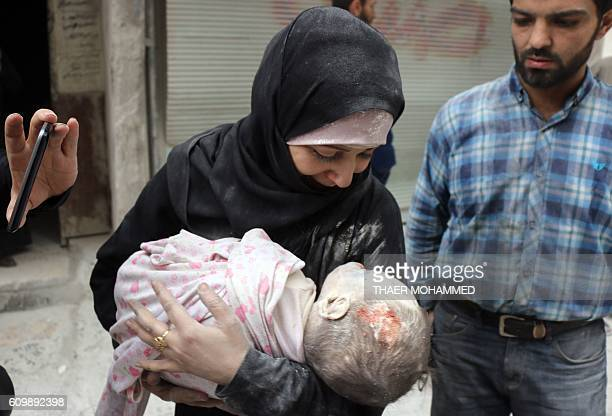 A Syrian woman carries the body of her infant after he was retrieved from under the rubble of a building following a reported airstrike on September...