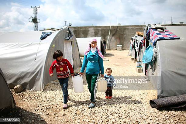 Syrian woman carries water with her children in a refugee camp on March 22 2015 in Suruc in the province of Sanliurfa Turkey Turkey has one of the...
