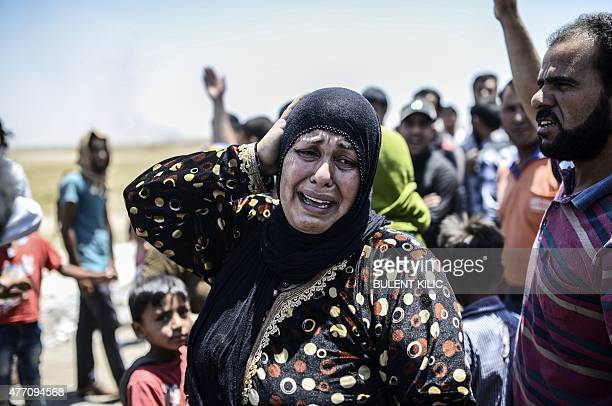 A Syrian woman cries after an airstrike hit the eastern part of the Syrian town of Tal Abyad at the Turkish crossing of Akcakale in the southeast...