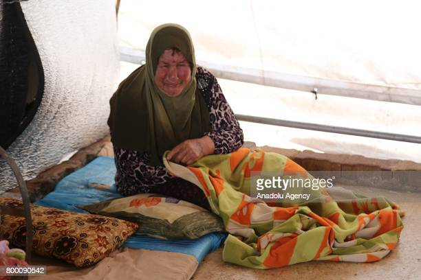 Syrian woman cries inside her tent during Muslim's holy month of Ramadan in Idlib Syria on June 23 2017 Ahead of Eid al Fitr Syrian people who fled...
