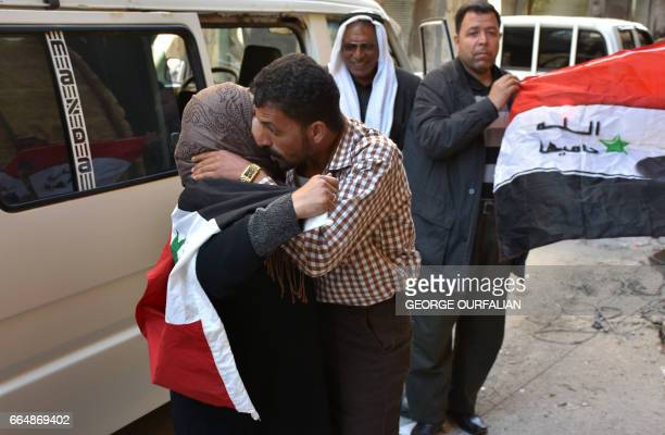 A Syrian woman embraces a relative who fled his hometown due to the fighting upon his return to Aleppo's Myassar neighbourhood on April 5 2017 / AFP...