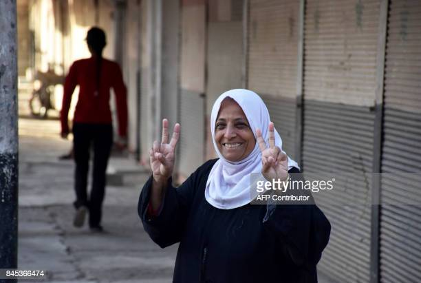 A Syrian woman flashed the sign for victory in the eastern city of Deir Ezzor on September 10 as Syrian government forces continue to press forward...