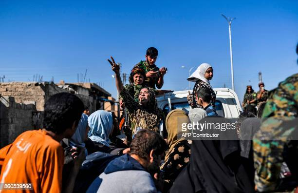A Syrian woman flashes the victory sign as civilians gather on the western front after fleeing the centre of Raqa on October 12 2017 Syrian...