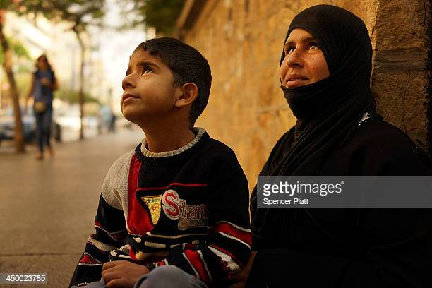 Syrian woman from the city of Latakia begs with her son in a wealthy district of Beirut on November 16 2013 in Beirut Lebanon As the war in...
