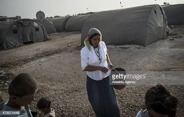 Syrian woman goes to fill the buckets with water in Suruc district of Sanliurfa, Turkey on May 28, 2015. Syrian refugees fled their home due to the...