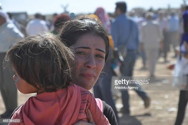 Syrian woman holding a child weeps as Syrians fleeing from clashes between the Islamic State of Iraq and Levant militants and Democratic Union Party...