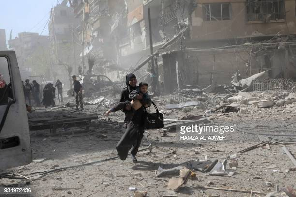 Syrian woman holds a child and runs for cover following Syrian government air strikes on the Eastern Ghouta rebel-held enclave of Douma, on the...