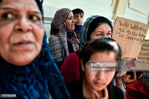 A Syrian woman holds a placard reading 'We want to go to our father in Germany' outside the German embassy in Athens on July 19 2017 during a protest...