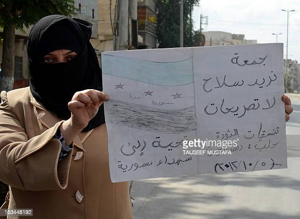 A Syrian woman holds a sign calling for the arming of rebels during a protest against the regime in the northern city of Aleppo on October 5 2012...