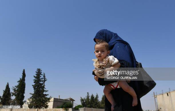 A Syrian woman holds her child as she walks at the Abu Duhur crossing on the eastern edge of Idlib province on August 20 2018 Civilians are coming...
