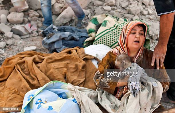A Syrian woman holds her dead baby as she looks over at her dead husband's body following an airstrick by regime forces on the town of Azaz near the...