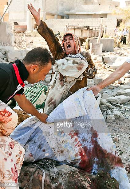 A Syrian woman holds her dead baby as she screams upon seeing her husband's body following an airstrick by regime forces on the town of Azaz near the...