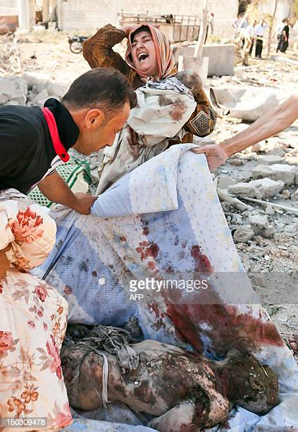 A Syrian woman holds her dead baby as she screams upon seeing her husband's body being covered following an airstrick by regime forces on the town of...