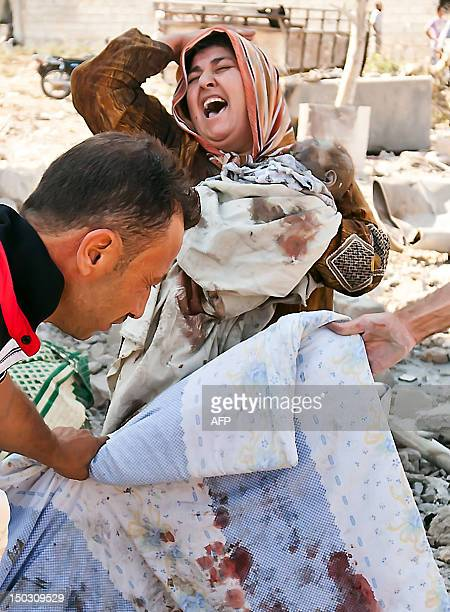 Syrian woman holds her dead baby as she screams upon seeing her husband's body being covered following an airstrick by regime forces on the town of...