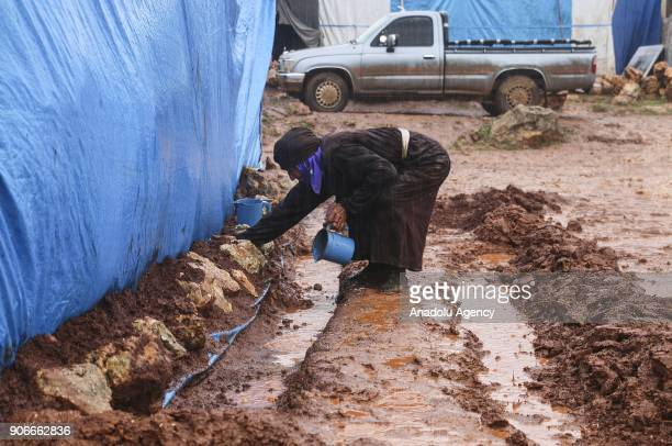 Syrian woman is seen near her tent through mud at a refugee camp where many Syrians lived in following the heavy rains in Idlib Syria on January 18...