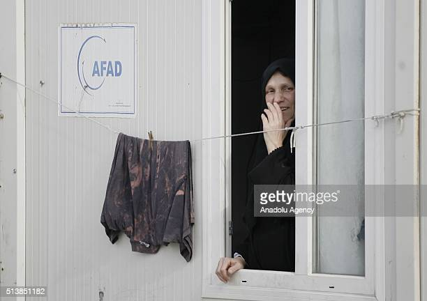 Syrian woman looks through a window of container home at the container city housing 1340 women and more than two thousands children who fled war in...