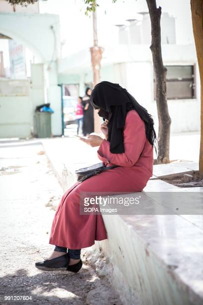 Syrian woman on her phone at a Syrian community center in Mafraq There are about 14 million Syrian refugees in Jordan and only 20 percent are living...