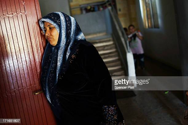 Syrian woman pauses in the entrance to the apartment she is sharing with other refugees in a poor neighborhood with a high concentration of Syrian...