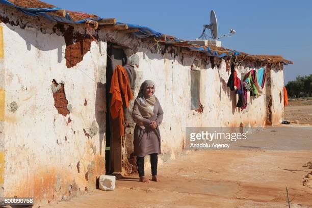Syrian woman poses barefoot in front of a tumbledown house during Muslim's holy month of Ramadan in Idlib Syria on June 23 2017 Ahead of Eid al Fitr...