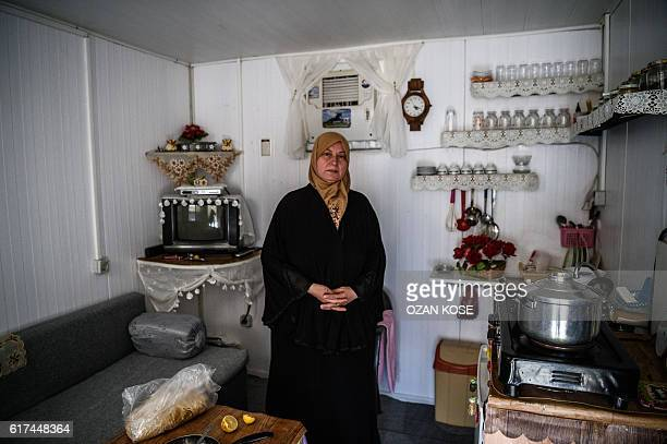 A Syrian woman poses inside her prefabricated home at a refugee camp in the Kilis district of Gaziantep southeastern Turkey on October 23 2016...
