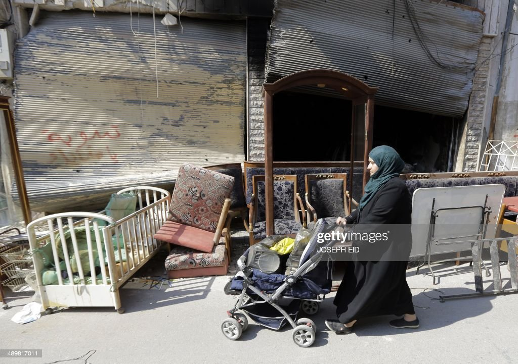 A Syrian woman pushes a baby stroller packed with belongings past furniture  laying on the side. A Syrian woman pushes a baby stroller packed with belongings past