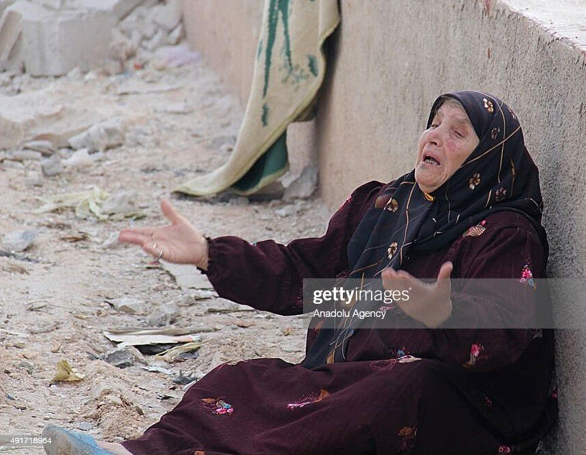 A Syrian woman reacts after her home were damaged by the Russian air strikes in Maasaran town, Idlib, Syria on October 07, 2015.
