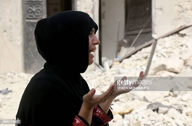 A Syrian woman reacts following a reported barrel bomb attack on the Bab alNairab neighbourhood of the northern Syrian city of Aleppo on August 25...