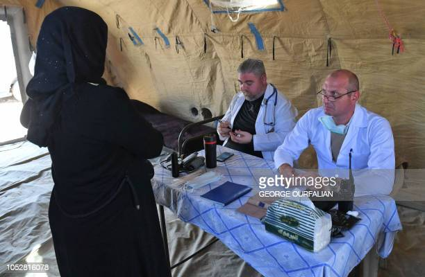 A Syrian woman receives a medical consultation from a Russian medical team at the Abu Duhur crossing on the eastern edge of Idlib province on October...