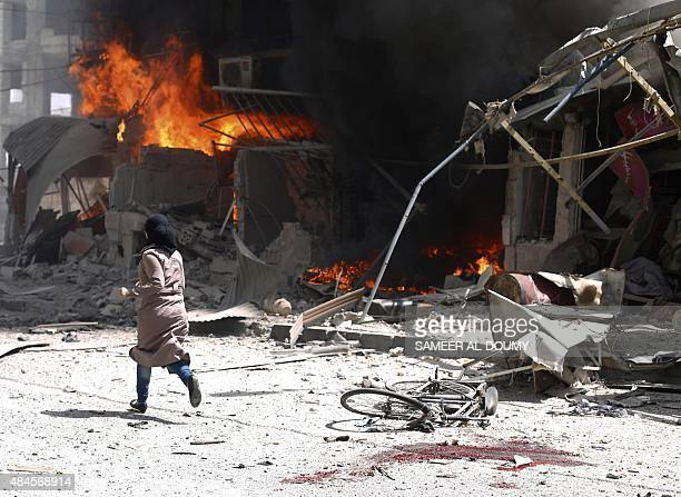 Syrian woman runs past blood stains and debris following air strikes by government forces on the rebel-held town of Douma on August 20, 2015. Human...