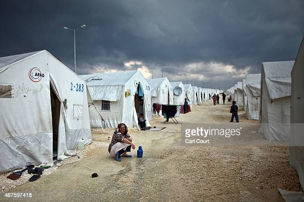 Syrian woman squats near her tent in Suruc refugee camp on March 25 2015 in Suruc Turkey The camp is the largest of its kind in Turkey with a...