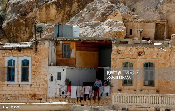 A Syrian woman stands on a balcony in the ancient Christian town of Maalula 56 kilometres northeast of the Syrian capital Damascus on May 13 2019 The...