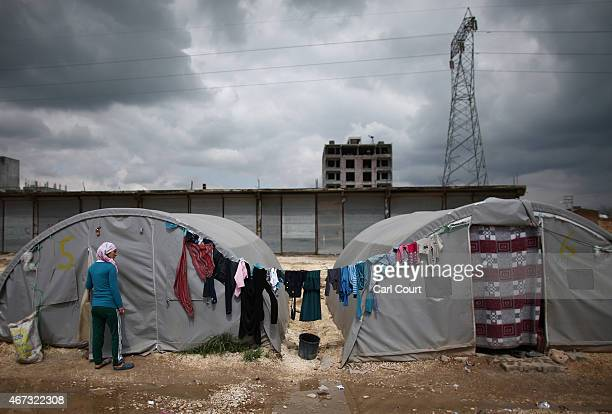 Syrian woman stands outside her tent in a refugee camp on March 22 2015 in Suruc in the province of Sanliurfa Turkey Turkey has one of the largest...