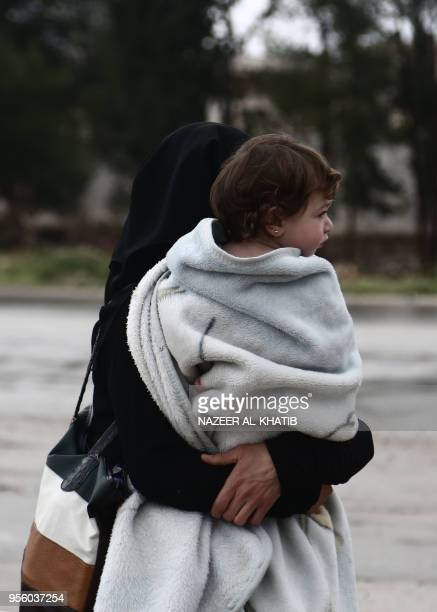 A Syrian woman walks carrying a child upon arriving in a convoy at Abu alZandin checkpoint near alBab in northern Syria on May 8 after being...
