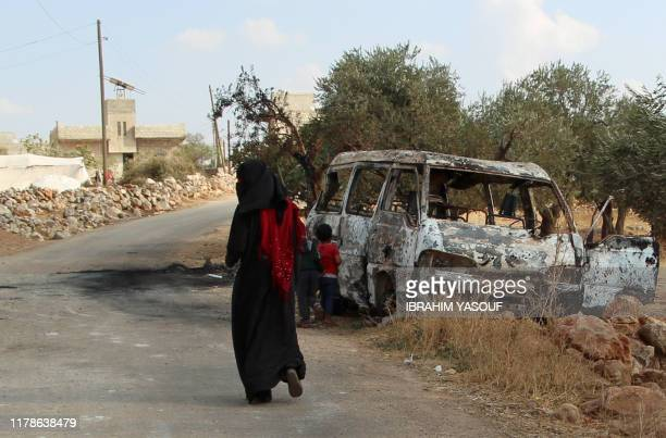 Syrian woman walks past a damaged van at the site of helicopter gunfire which reportedly killed nine people near the northwestern Syrian village of...