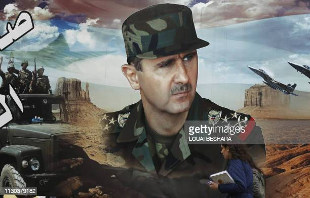 Syrian woman walks past a portrait of Syrian President Bashar al-Assad in Bab Tuma in the old city of Damascus on March 14, 2019. - Assad has won his...