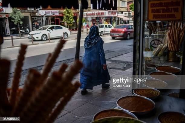 A Syrian woman walks past a shop on May 1 2018 in Gaziantep southwestern Turkey In the Turkish city of Gaziantep home to around half a million...