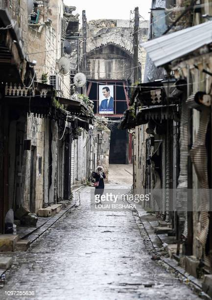 A Syrian woman walks past damaged stores in an alley in the Bab alQinnasrin area in Aleppo's Old city on February 10 2019