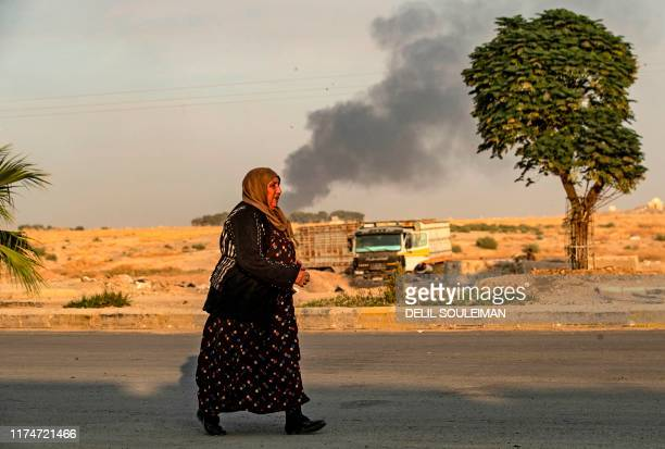 Syrian woman walks past smoke as Arab and Kurdish civilians flee following Turkish bombardment on Syria's northeastern town of Ras alAin in the...