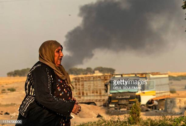 A Syrian woman walks past smoke as Arab and Kurdish civilians flee following Turkish bombardment in Syria's northeastern town of Ras alAin in the...