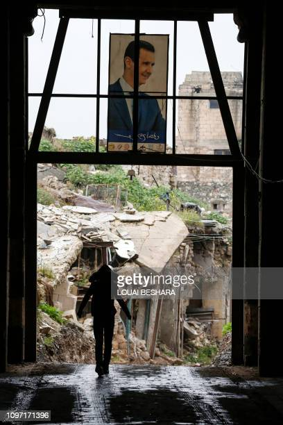 A Syrian woman walks through an entrance of an alley in the Bab alQinnasrin area in Aleppo's Old city on February 10 2019