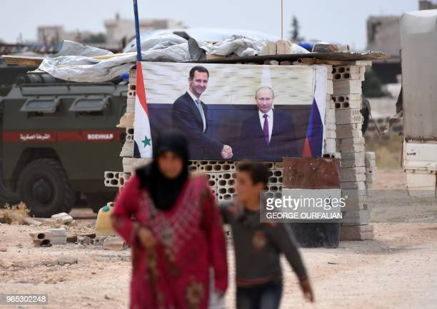 A Syrian woman walks with a boy past a banner showing Russian President Vladimir Putin shaking hands with Syrian President Bashar alAssad after...