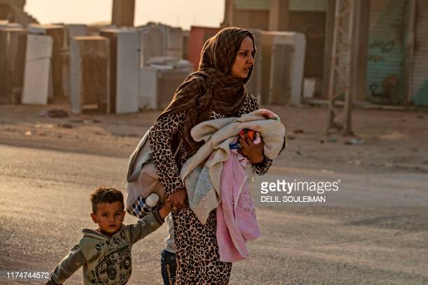 A Syrian woman walks with her children as Arab and Kurdish civilians amid Turkish bombardment on Syria's northeastern town of Ras alAin in the...