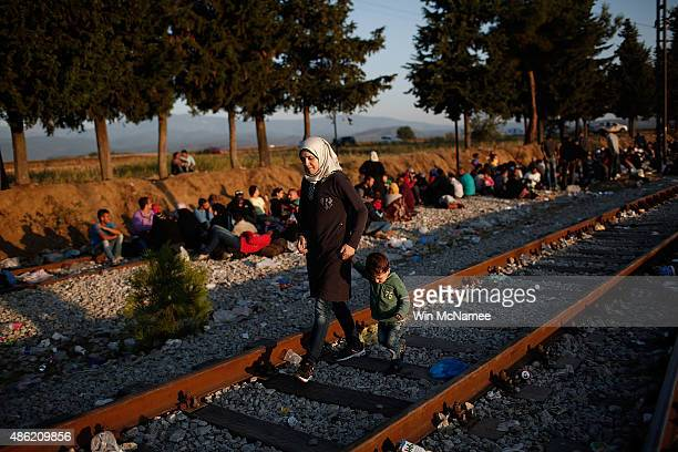 Syrian woman walks with her son along railroad tracks while waiting to be processed across a border crossing for migrants on September 2 2015 in...