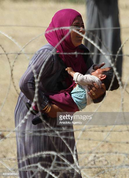 Syrian woman with her baby fled from clashes between the Islamic State of Iraq and Levant militants and Democratic Union Party forces in the...