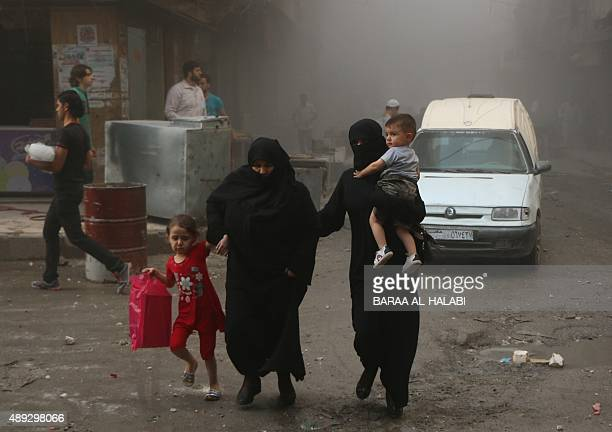 Syrian women and children walk in a dusty street following an air strike by government forces on the rebel held Bustan alQasr district in the east of...