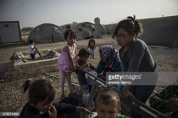 Syrian women and girls fill the buckets with water in Suruc district of Sanliurfa, Turkey on May 28, 2015. Syrian refugees fled their home due to the...